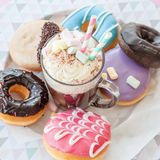 Hot chocolate and donuts. Hot chocolate with whipped cream and colorful donuts Stock Photo