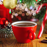 Hot chocolate drink. Cup of hot cocoa beverage under Christmas tree, gift boxes on background. Traditional hot chocolate beverage Stock Image