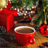 Hot chocolate drink. Traditional winter hot chocolate drink near gift boxes under Christmas tree. Delicious cocoa beverage on a table Stock Images