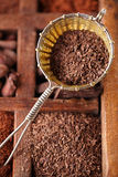 Hot chocolate flakes  in old rustic style silver sieve on wooden Stock Image
