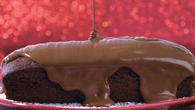 Hot chocolate flowing on chocolate cake on red background stock video footage