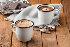Hot chocolate with foam in two mugs. Hot chocolate with foam in two enamel mugs Royalty Free Stock Photos