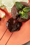 Hot Chocolate Fondant. With Mint Leaves and Berries on Terracotta Plate Close Up. Fresh Brownie Dessert with Melted Dark Cocoa Mousse. Small Chocolate Cake with royalty free stock photos