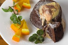 Chocolate fondant on a plate. Hot chocolate fondant on a plate with mint, oranges and ice cream royalty free stock photos