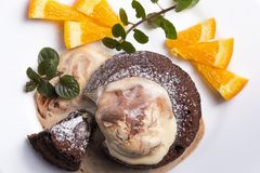 Chocolate fondant on a plate. Hot chocolate fondant on a plate with mint, oranges and ice cream stock images