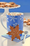 Hot chocolate and ginger cookies. Hot chocolate with marshmallows and snowflake shape gingerbread cookies Stock Photo
