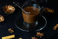 Hot chocolate in a glass cup. On a dark background, star anise, cinnamon Stock Image
