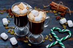 Hot chocolate in the glasses with marshmallows decorated with heart of green candy cones and winter spices - cinnamon, cardamom. And anise on the black wooden stock photo