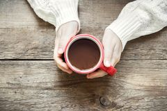 Hot chocolate in hands. Female hands holding red mug of hot chocolate coffee on rustic wooden background with copy space stock photography