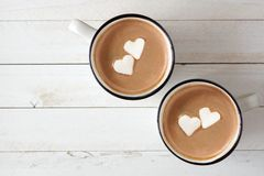 Hot chocolate with heart marshmallows over white wood stock photos