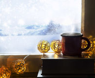 Hot chocolate indoor with books and lights on frozen winter land Stock Photos