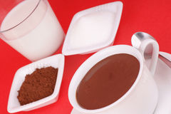 Hot chocolate ingredients. Hot chocolate served in a white cup and the ingredients to prepare it: milk, sugar and cocoa. Studio shot over red background Royalty Free Stock Images