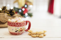 Hot chocolate with marshmallow candies. Christmas cookies shaped in snowflakes,  golden cones and christmass tree lights. White wo Royalty Free Stock Photos