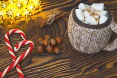 Hot chocolate with marshmallows, candy, spices and nuts on grunge dark table. Christmad card Royalty Free Stock Images