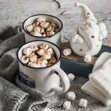 Hot chocolate with marshmallows, ceramic Santa Claus, old book and gloves, bright wooden surface Royalty Free Stock Photo