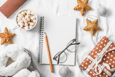 Hot chocolate with marshmallows and cinnamon, clean blank notepad, gift box on a light background. Christmas inspiration planning Royalty Free Stock Photo