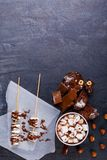 Hot chocolate with marshmallows in a cup with other sweets on the table royalty free stock images