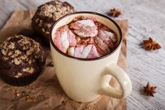 Hot chocolate with marshmallows and cupcakes on a table background. Coffee and muffins. Winter cafe desserts. stock photography