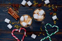 Hot chocolate with marshmallows decorated with hearts of candy cones and winter spices - cinnamon, cardamom and anise. On the wooden background. Top view stock photo