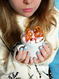 Hot chocolate with marshmallows in girl`s hands. A girl wearing knitted sweater is holding a mug of hot chocolate decorated with marshmallow and pretzels stock photo