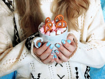 Hot chocolate with marshmallows in girl`s hands. A girl wearing knitted sweater is holding a mug of hot chocolate decorated with marshmallows and pretzels stock image