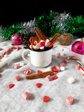 Hot chocolate with marshmallows. New Year composition made of hot chocolate, Christmas tree decorations and candy canes stock photo