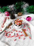 Hot chocolate with marshmallows. New Year composition made of hot chocolate, Christmas tree decorations and candy canes royalty free stock images