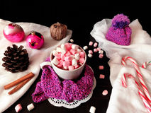 Hot chocolate with marshmallows. New Year composition made of hot chocolate, knitted kit, Christmas tree decorations and candy canes stock images