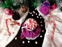 Hot chocolate with marshmallows. New Year composition made of hot chocolate, knitted kit, Christmas tree decorations and candy canes stock photos