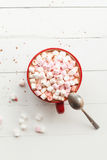 Hot chocolate with marshmallows in red cup on table. Hot chocolate with marshmallows in red cup on wood table Stock Image