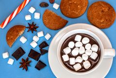 Hot chocolate with marshmallows and various sweets on a blue bac Royalty Free Stock Photos