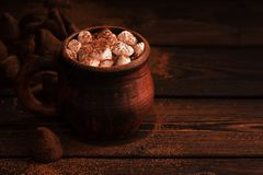 Hot chocolate with marshmallows in a vintage cup with chocolate truffles on a wooden rustic plank table. Selective focus. Dark. Food photo,copy space royalty free stock images