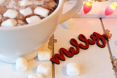 Hot chocolate with marshmallows on white wood. Hot chocolate in a white mug with marshmallows, red lights, and a Merry sign against a rustic wood background Stock Image