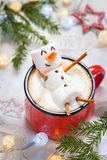 Hot chocolate with melted marshmallow snowman. Red mug with hot chocolate with melted marshmallow snowman Stock Image