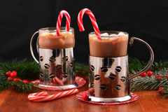 Hot chocolate with mini marshmallows. Cheery Christmas mugs of hot chocolate with mini marshmallows and peppermint candy canes on dark background with room for Royalty Free Stock Image
