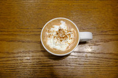 Hot chocolate in a mug of white on a brown wooden table Royalty Free Stock Photos