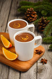 Hot chocolate with orange and spices on the rustic wooden table Stock Image