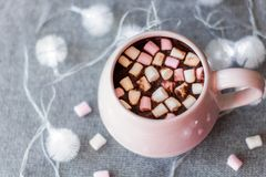 Hot chocolate in  pink ceramic mug with marshmallows. Hot chocolate  pink ceramic mug marshmallows and garland  gray knitted background Stock Photography
