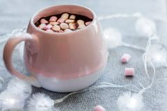 Hot chocolate in  pink ceramic mug with marshmallows. Hot chocolate  pink ceramic mug marshmallows and garland  gray knitted background Stock Photos