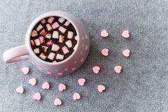 Hot chocolate in  pink ceramic mug with marshmallows. Hot chocolate  pink ceramic mug marshmallows and heart shaped pink chocolate candies  gray knitted Stock Image