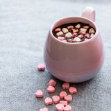 Hot chocolate in  pink ceramic mug with marshmallows. Hot chocolate  pink ceramic mug marshmallows and heart shaped pink chocolate candies  gray knitted Royalty Free Stock Images
