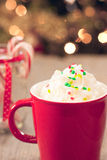 Hot chocolate in a red mug. A red cup full of hot chocolate is covered in a mound of whipped cream and green and red festive sprinkles. It rests in front of a Stock Image