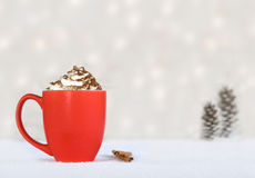 Hot chocolate in a red mug - winter treat. Hot chocolate in a red mug on a winter background Royalty Free Stock Photo