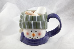 Hot chocolate in a snowman mug. Hot chocolate (cocoa) in a mug made to look like a snowman.  Background is fake snow Royalty Free Stock Photography