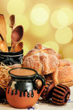 Hot chocolate and sweet bread pan de muerto. Jar of hot chocolate and sweet bread pan de muerto with wooden chocolate grinder and spoons on festive background Royalty Free Stock Photo