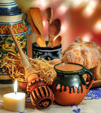 Hot chocolate and sweet bread pan de muerto. Jar of hot chocolate and sweet bread pan de muerto with wooden chocolate grinder and spoons on festive background Royalty Free Stock Images