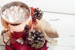 Hot chocolate. Topped with marshmallow and served in a shiny copper mug. On a white wooden table with autumn leaves, pine cone and wooden table decoration Royalty Free Stock Photo