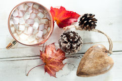 Hot Chocolate. Hot chocolate, topped with marshmallow and served in a shiny copper mug. On a white wooden table with autumn leaves, pine cone and wooden table Stock Photos