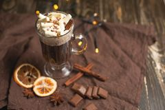 Hot chocolate in a transparent mug with whipped cream and cinnamon sticks, spices, nuts and cocoa powder on a rustic wooden backgr stock images