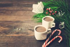 Hot chocolate in two cups with lollipops, fir tree and toy house. Over wooden background, toned photo Stock Images